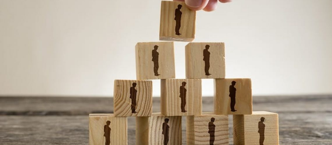 Man stacking a tower of wood blocks with human silhouettes, human resources and management concept.